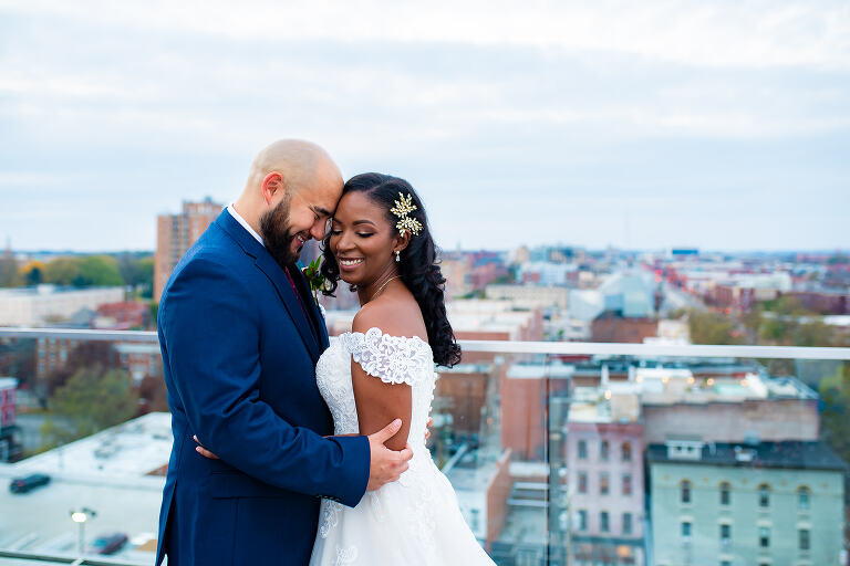 A bi-racial couple embraces on the Quirk Hotel rooftop in downtown Richmond, Virginia on their wedding day.